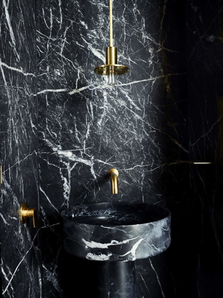 The powder room is done with brass and black marble for a chic look