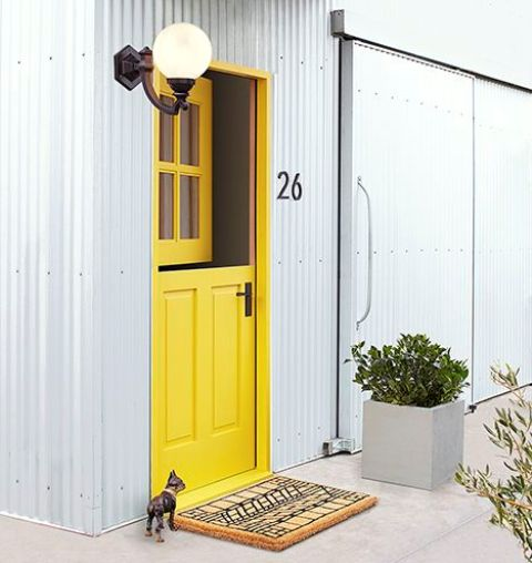 a creative entrance with a bright yellow Dutch door and a fun pritned rug