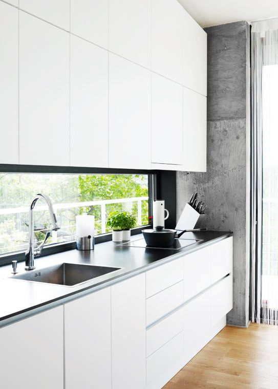 a minimalist white kitchen with a black framed window backsplash for a more catch and peaceful look