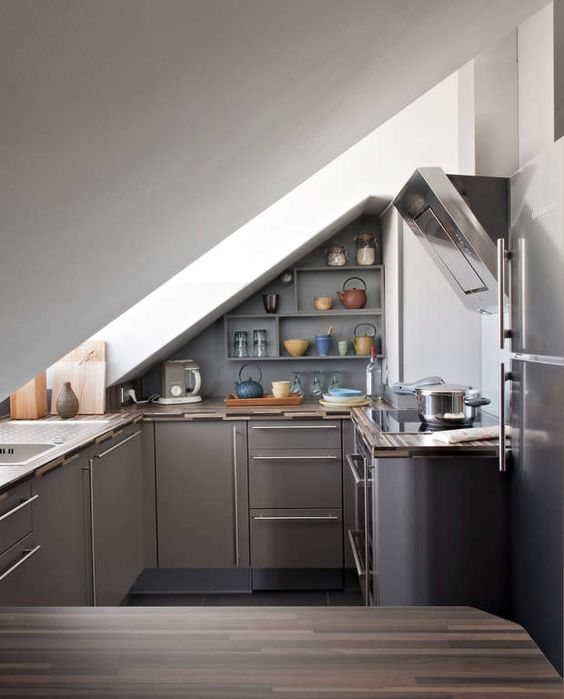 a small attic industrial kitchen with grey cabinets and stainless steel with a large skylight