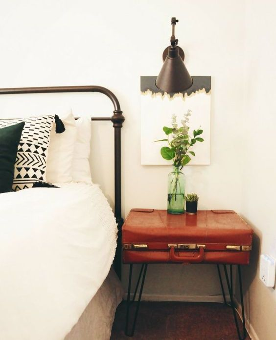 a vintage suitcase placed on trendy hairpin legs gives a cool boho chic nightstand