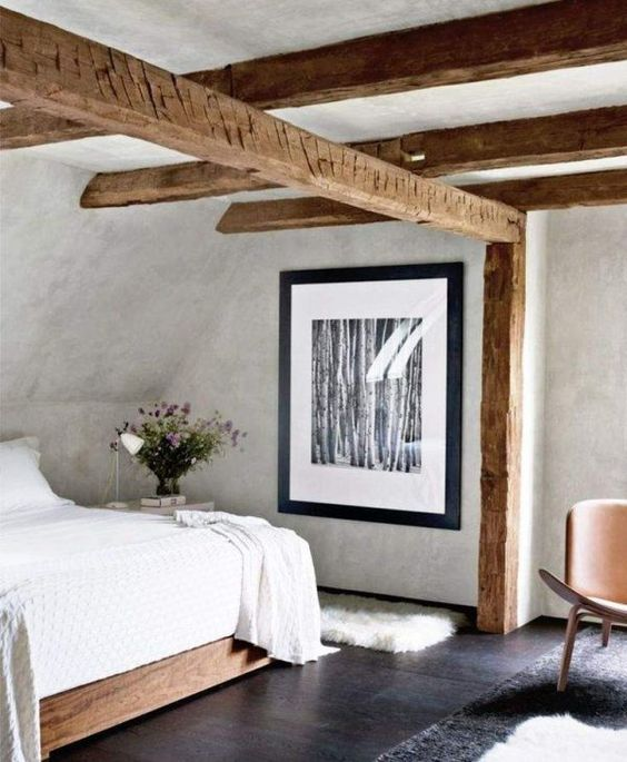 off-white plaster walls and a ceiling plus wooden beams bring a vintage feel and modern furniture for an edgy touch