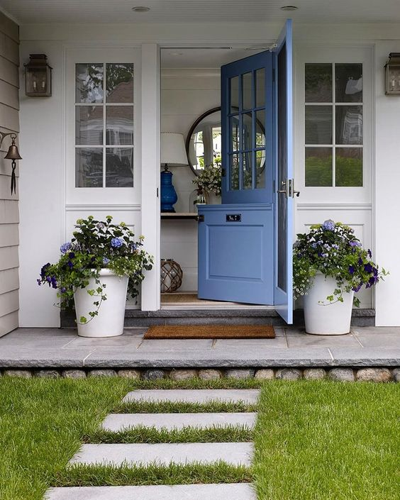 a cute blue Dutch door and matching potted flowers on both sides to make the entrance welcoming