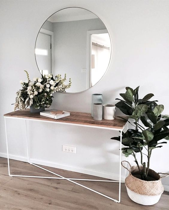 a minimalist summer console table with lush blooms in a vase and a potted plant in a basket - you won't need more