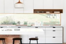 12 a minimalist white kitchen with a window backsplash that brings light in and lets enjoy the views