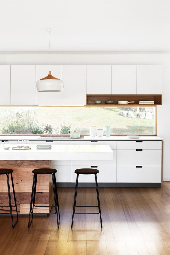 a minimalist white kitchen with a window backsplash that brings light in and lets enjoy the views
