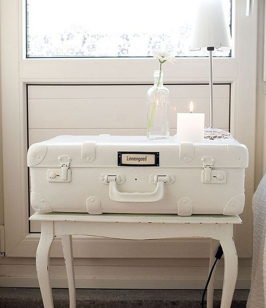 a vintage suitcase painted white and put ona  white table for a shabby chic bedroom