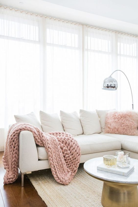 an all-white living room is injected with blush pink accessories and touches of metallics