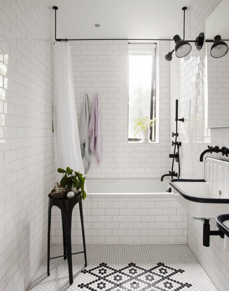 The bathroom is done with white tiles with black grout for a chic and otustanding look