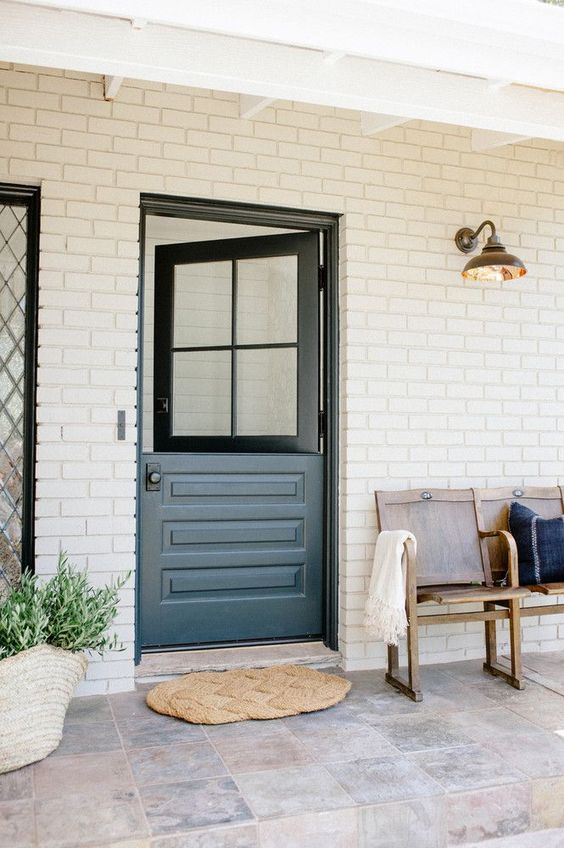 a farmhouse entrance with a bench, a graphite grey Dutch door and a jute rug
