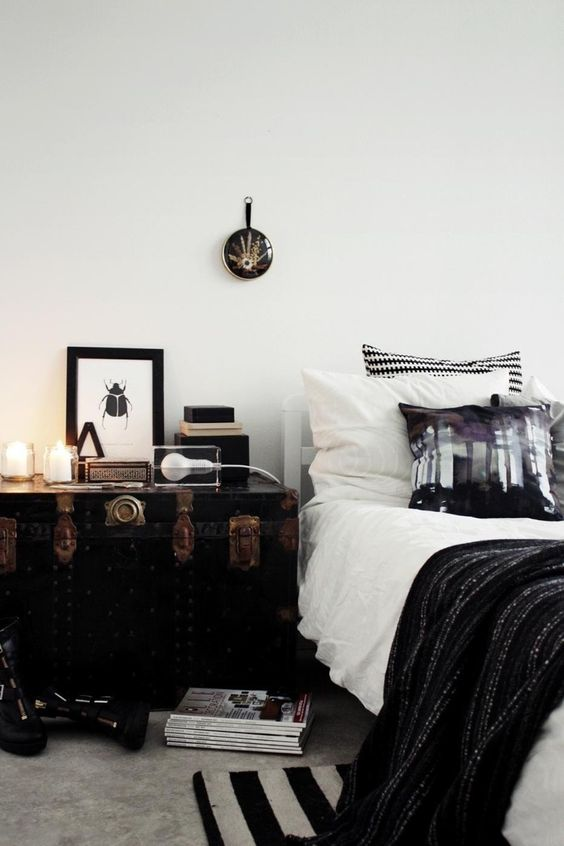 a large vintage chest painted black brings a unique personalized touch to the bedroom