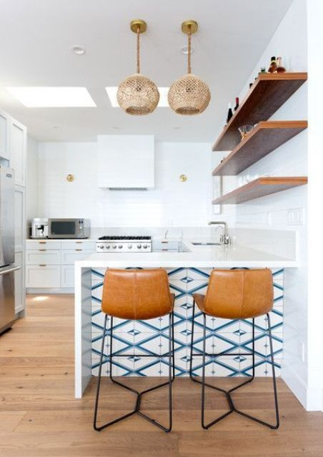 a modern coastal kitchen with wicker pendants and blue mosaic tiles on the kitchen island