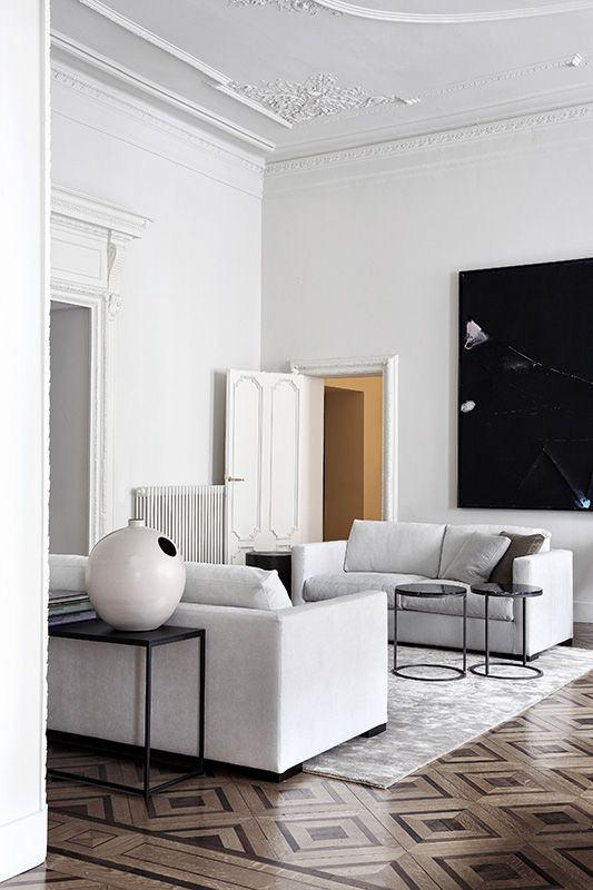 a refined monochromatic living room with two white sofas and some black touches
