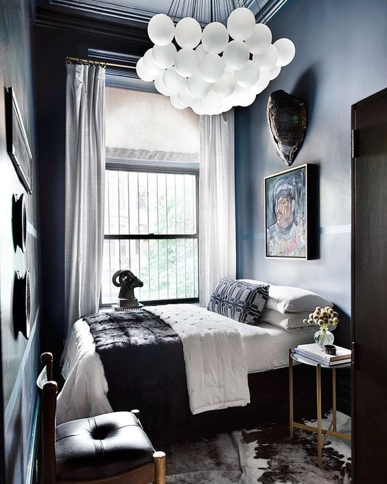 a large and bold chandelier makes a statement in this moody lux guest bedroom