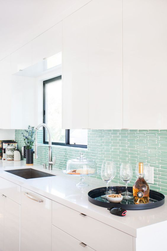 a minimalist kitchen with an aqua tile backsplash is a fresh take on a coastal kitchen