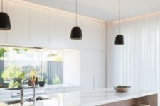 14 a white minimalist kitchen with wooden touches and a window backsplash for much light in the space