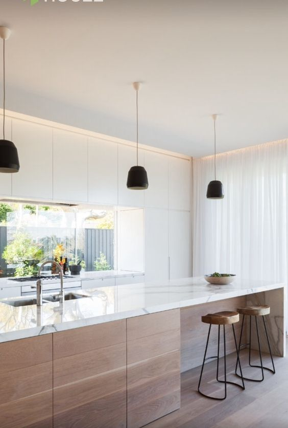 a white minimalist kitchen with wooden touches and a window backsplash for much light in the space
