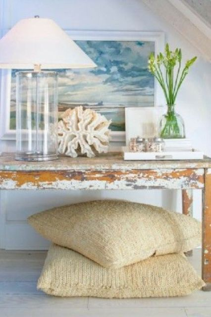 a distressed console table, a glass lamp, a large coral and a seascape artwork for a dreamy feel