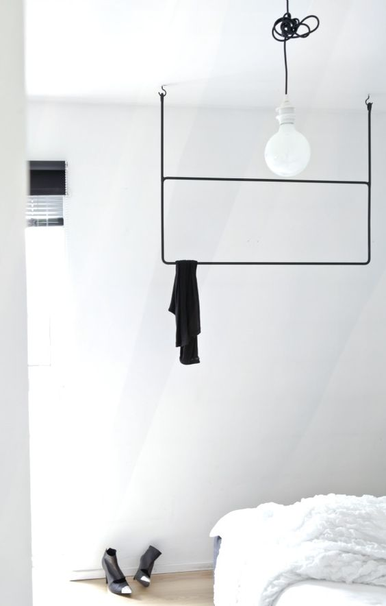 a minimalist black rack with two shelves attached to the ceiling for a Scandinavian space