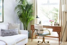 15 a modern boho space with a convertible sofa and a mid-century wooden desk by the window