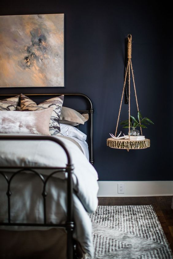 a moody bedroom with a hanging bedside table of a raw edge wood slice and twine for a rustic touch