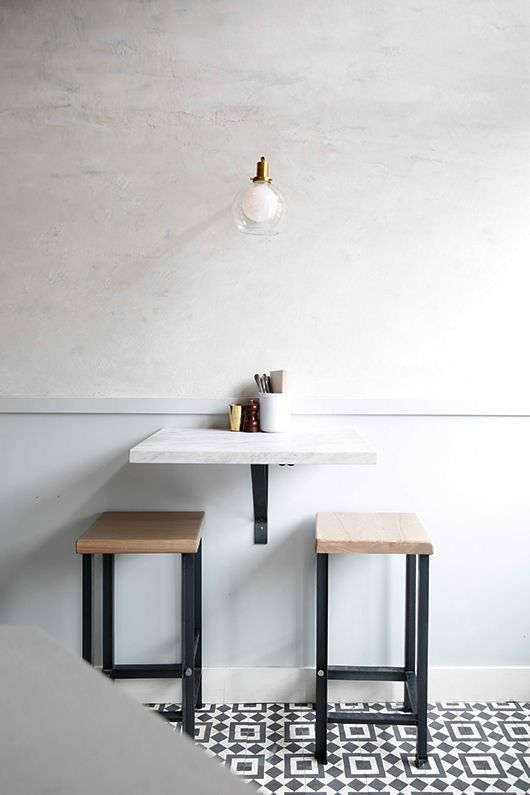 a small breakfast space with a wall-mounted table and a couple of matching stools plus a lamp over it