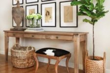 15 a summer console with baskets around, a wooden sculpture, greenery and vintage botanical artworks