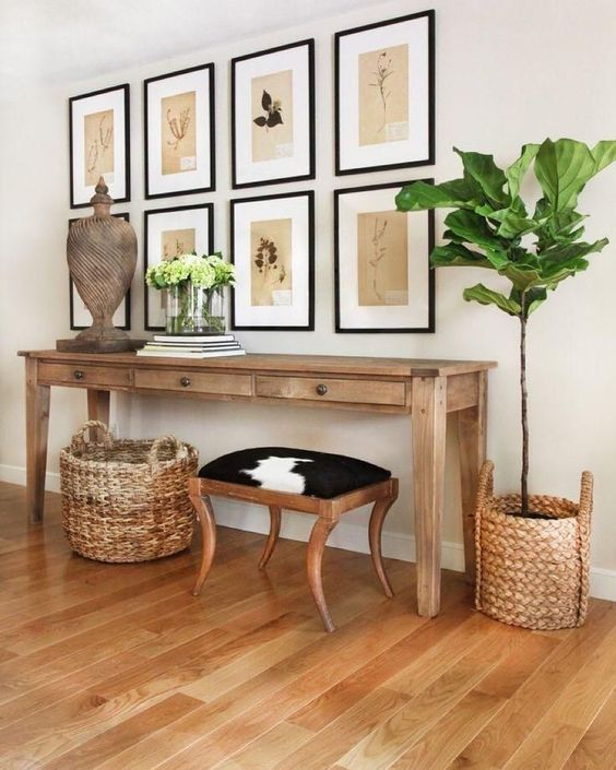 a summer console with baskets around, a wooden sculpture, greenery and vintage botanical artworks