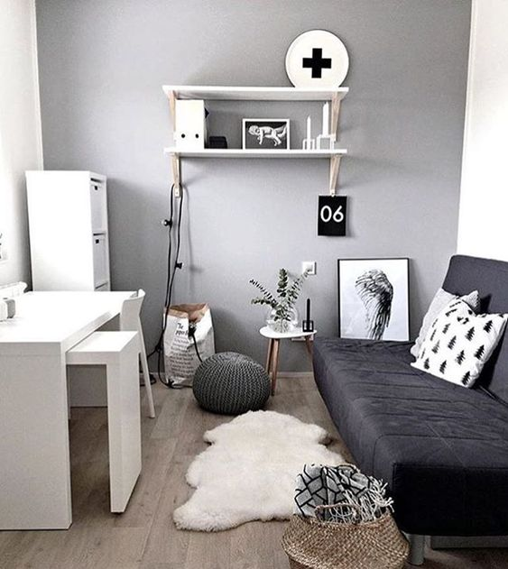 a Scandinavian bedroom with a black transformable sofa and a white desk plus some drawers