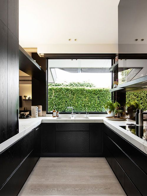 a black and white space with a large window that lets you enjoy the garden views