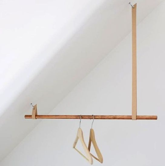 a creative idea for an attic space of a wooden stick and some leather loops looks chic