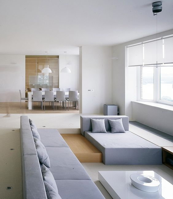 a minimalist sunken living room with geometric furniture and a view
