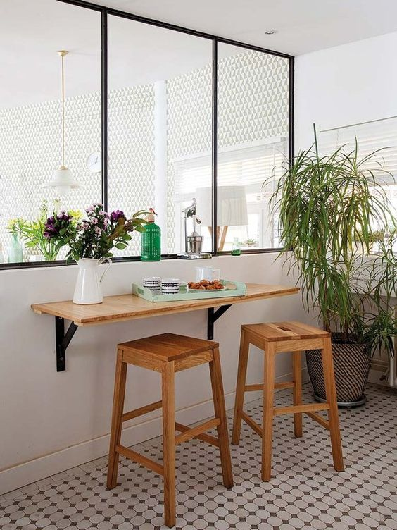 a small breakfast space with a wall-mounted tabletop, wooden stools and some greenery around it