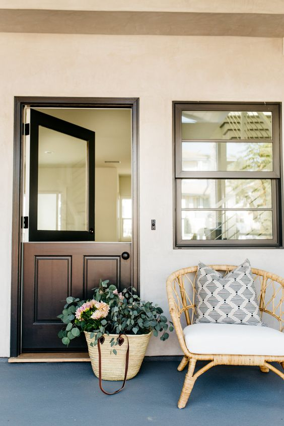 a stylish contemporary meets rustic entrance with a black Dutch door with a solid glass insert