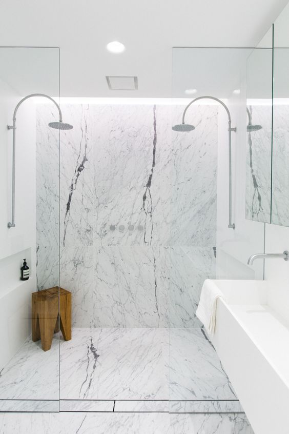 white marble tiles and a wooden stool bring texture and eye catchiness to the space