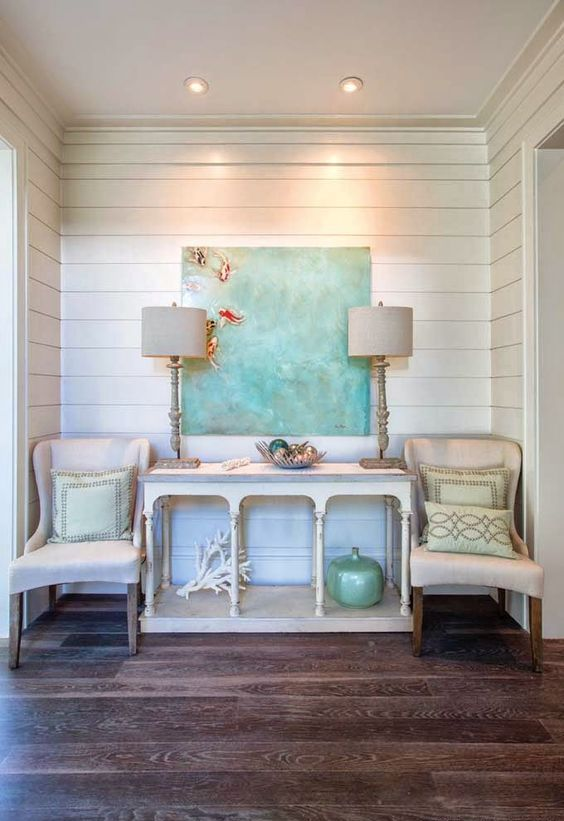 a beach console table, a coral, a bottle, a driftwood bowl and an oversized artwork