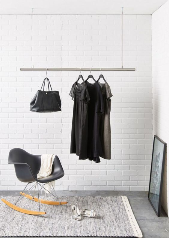 a ceiling rack of a metal pipe and ropes for a modern monochrome space