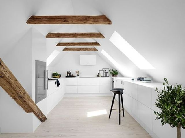a minimalist white space with wooden beams and many skylights that fill the space with light