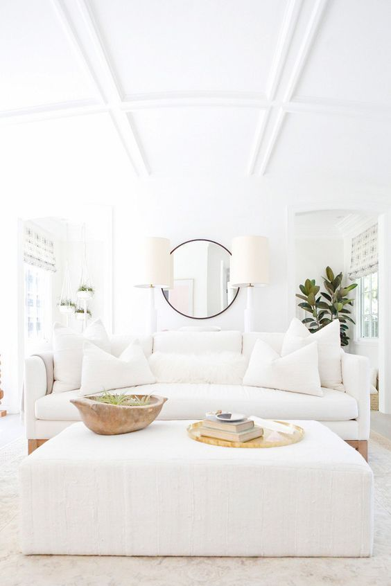a modern white sofa with matching pillows on wooden legs looks fresh and non-boring