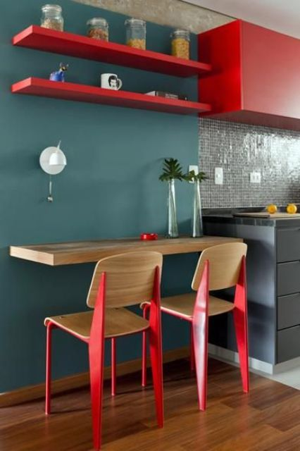a small colorful breakfast space with a wall-mounted tabletop and shelves over the space