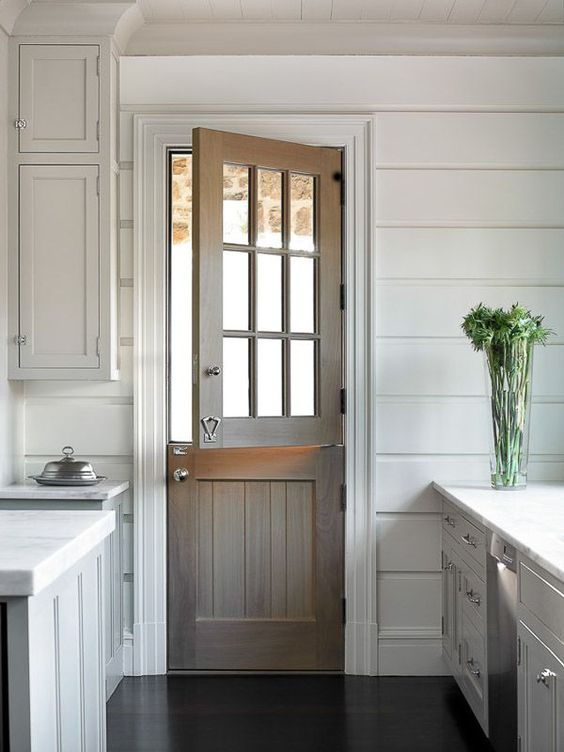 a stained wood Dutch door adds a rustic feel to the all-white kitchen with paneling