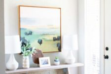 17 a summer console with an abstract artwork, baskets and greenery for a cozy feel