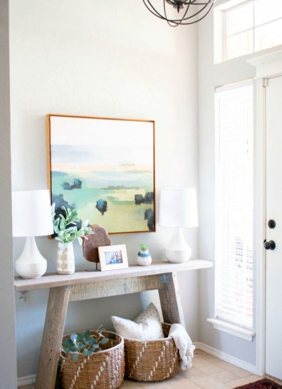 a summer console with an abstract artwork, baskets and greenery for a cozy feel
