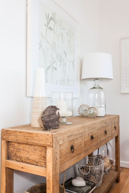 a beach console, a glass base lamp, a fish of driftwood and some floats