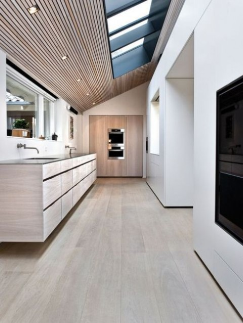 a minimalist kitchen done with wood and with several skylights plus additional lights to make the space cmfier