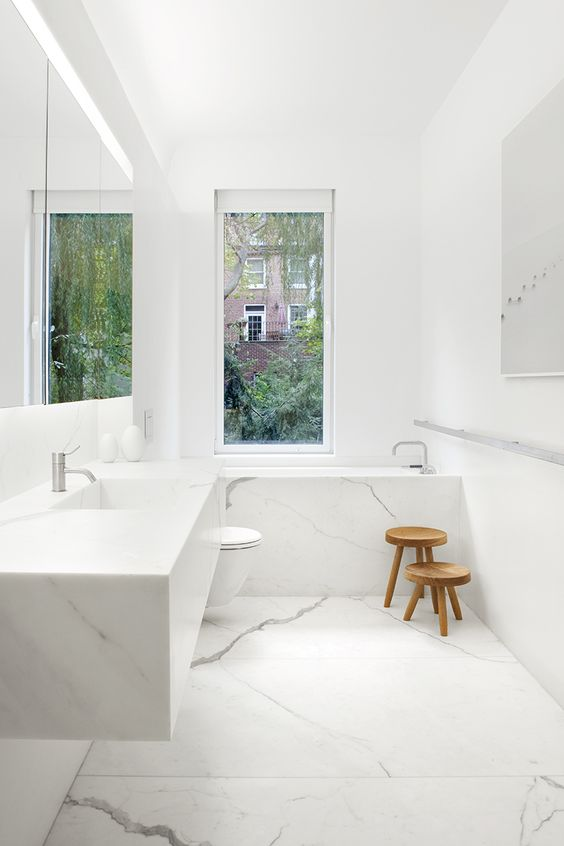 a minimalist white marble bathroom with a narrow window and a couple of wooden stools