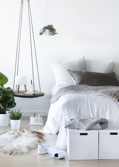 a serene bedroom with a wood slice hanging bedside table and a storage bench