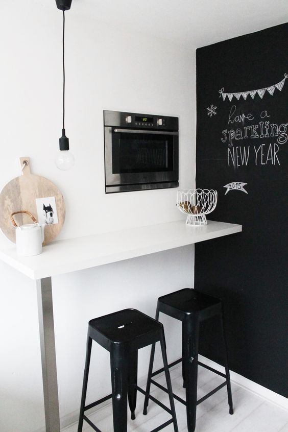a tiny breakfast nook with a wall-mounted table, black stools and a chalkboard wall