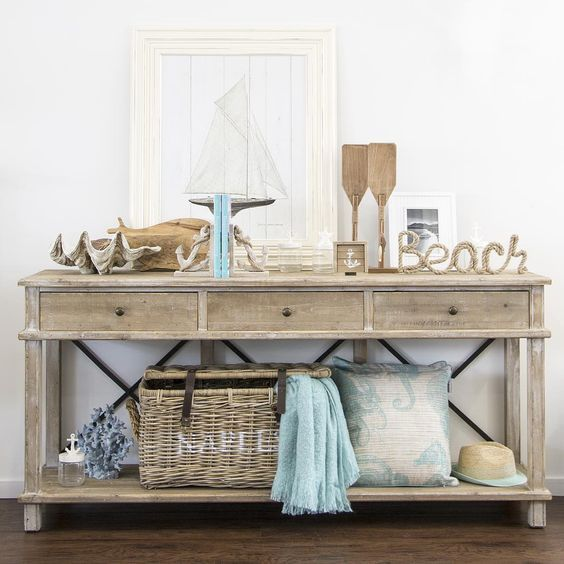a beach console, oars, a shell, a basket, a couple of beach-inspired artworks