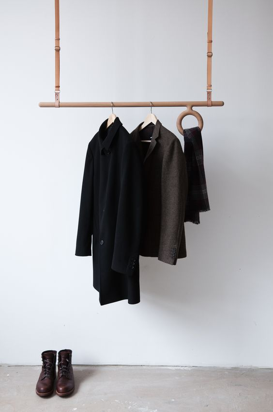 a creative wood and leather rack hanging from the ceiling with a ring for scarves